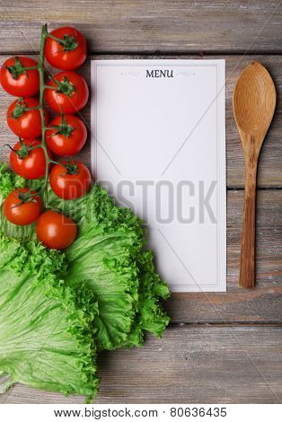 Menu sheet of paper with cherry tomatoes and lettuce on rustic wooden surface background poster
