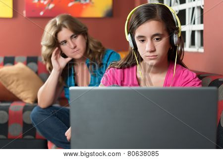Computer addiction - Teenage girl using a laptop and ignoring her worried mother