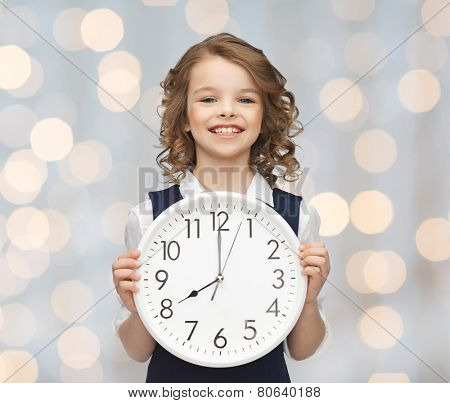 people, time management and children concept - smiling girl holding big clock showing 8 o'clock over holidays lights background