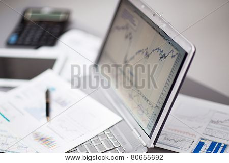 analyzing investment charts with laptop.