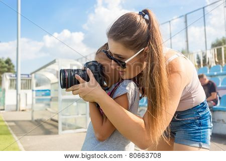 Woman Teaching Little Girl To Photograph Using Professional Camera