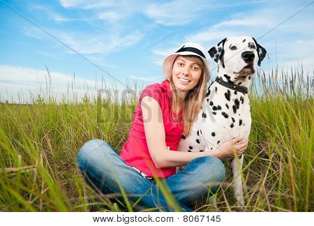 beautiful young woman in hat sitting in grass with her dalmatian dog pet smiling and looking into the camera poster