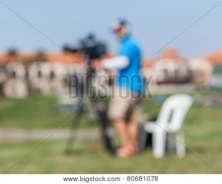 Blurred Background Of Sport Photographer Is Working During Golf Tournament For Live Broadcasting.