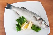 plate with sea bass lemon and parsley isolated on wooden background poster