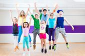 Dance teacher giving children Zumba fitness class in gym poster