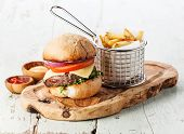 Burger with meat and French fries in basket on wooden background poster