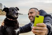 Man helping his grumpy dog firend to take a social media selfie image using a smartphone poster