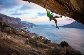 Male climber climbing overhanging rock against beautiful view of coast below poster