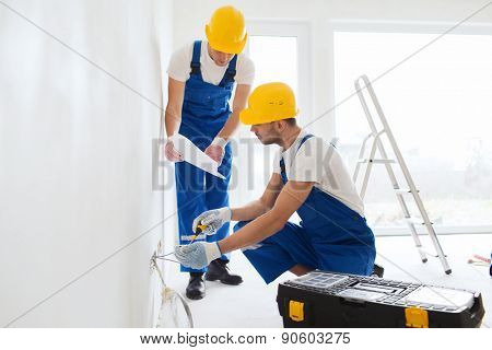 building, renovation, technology, electricity and people concept - two builders with tablet pc computer working with electricity indoors poster