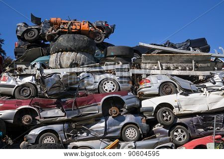 Low Angle View of Old Squashed Cars Stacked at Junk Yard with Blue Sky in Background poster