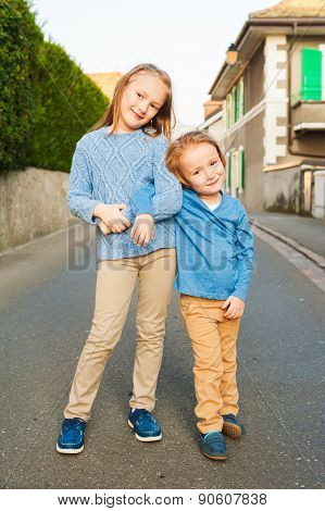 Two adorable kids in a city; girl and her little brother; wearing blue and beige clothes