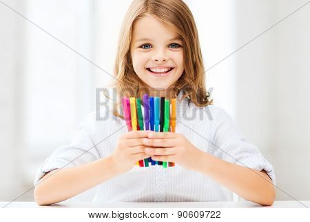 education and school concept - little student girl showing colorful felt-tip pens at school