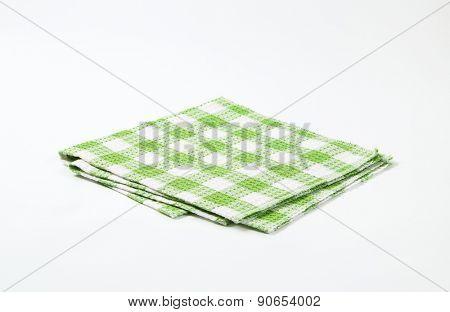 green and white checkered dishtowel on white background