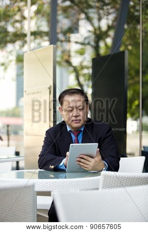 Senior Asian businessman using tablet