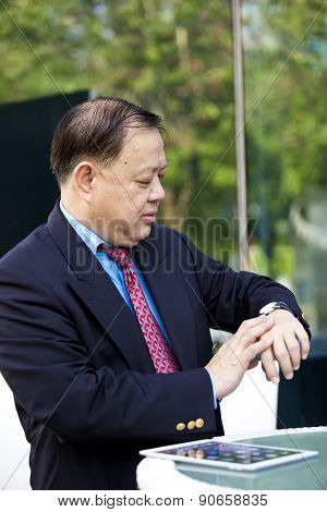 Asian businessman looking at watch