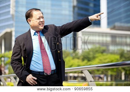 Asian businessman pointing at a direction