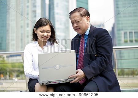 Asian businessman and young female executive using PC laptop