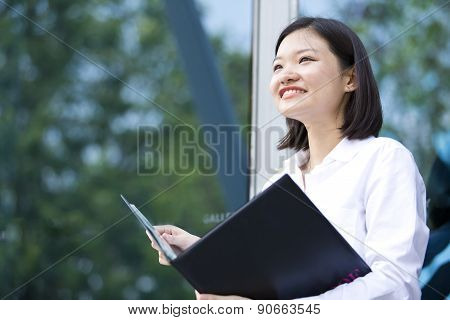 Young Asian female executive holding file