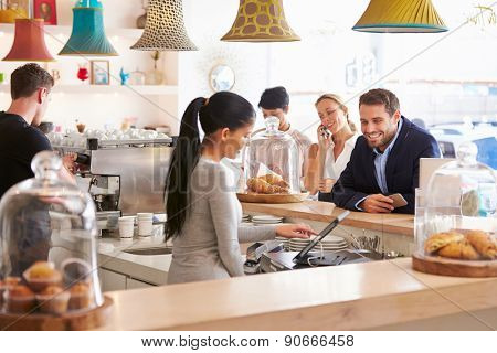 People ordering at the counter in a cafe
