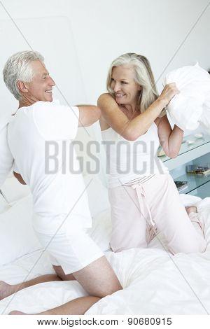 Senior Couple in bedroom having pillow fight