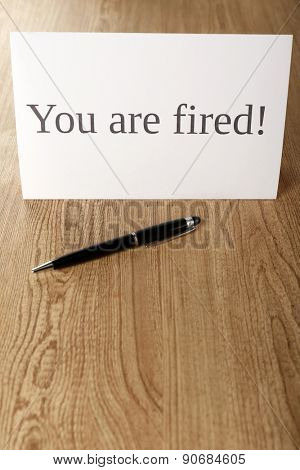 Message You're Fired on wooden background