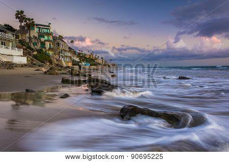 Waves Crashing On Rocks And Beachfront Homes In Laguna Beach, California.