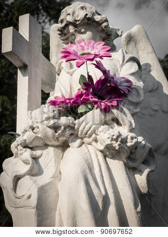 Mournful angel statue with flowers in cemetery