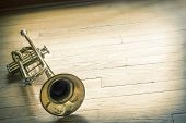Old rusty trumpet lays on wooden floor in the morning light poster