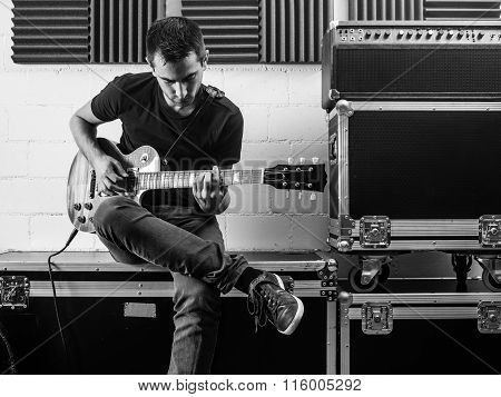 Playing His Guitar Backstage