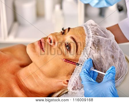 Woman middle-aged looking up is receiving injections in spa salon.