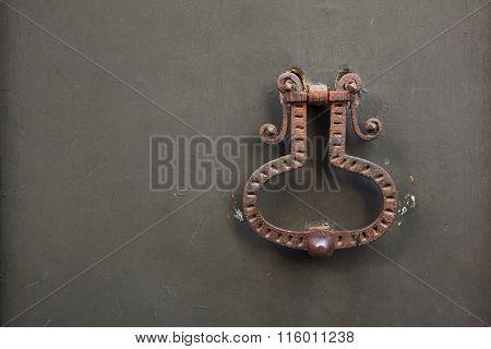 Old rusty doorknocker on the metal gate in Bergamo, Lombardy, Italy.