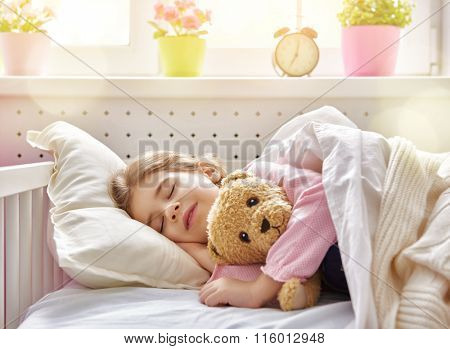 Adorable little child girl sleeping in the bed with her toy. The child girl hugs the teddy bear.