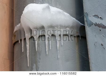Icicles hanging over a frozen water tube at roof. cold weather. Winter background. soft focus