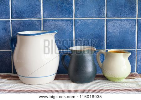 Still life with retro design ceramic jugs on napkin. Blue tiled wall background. Kitchen interior.