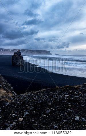 Rock on black sand beach