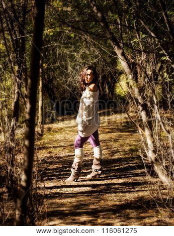 Natural attractive model standing between tree trunks with natural light