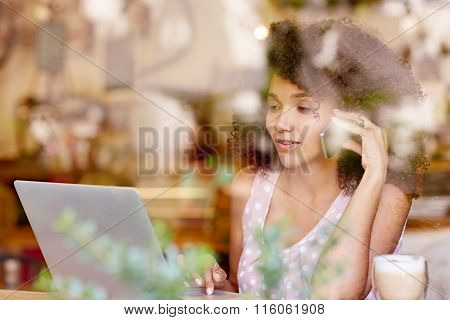 Woman typing her laptop and talking on phone
