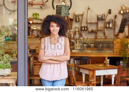 Small business owner standing in the door of her coffee