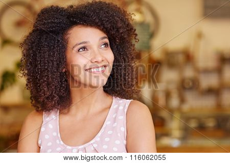Woman with curly afro dark hair smiling while looking up