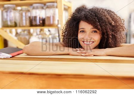 Beautiful waitress leaning on a wooden coffee shop counter