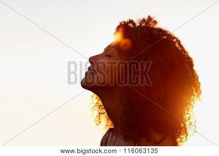 Profile of a woman with afro silhoutted against evening sun