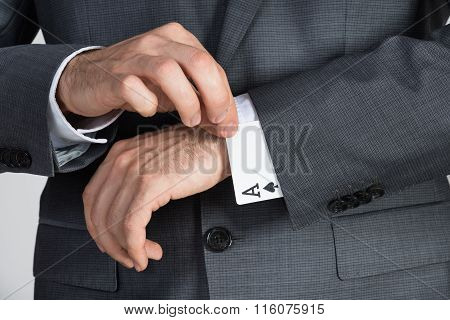 Businessman Removing Ace Cards From Sleeve