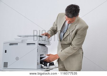 Businessman Removing Paper Stuck In Printer