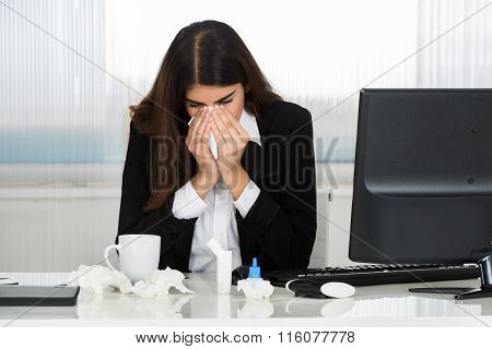 Sick Businesswoman Blowing Her Nose At Desk In Office
