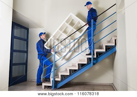 Movers Carrying Shelf While Climbing Steps
