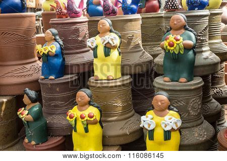 Traditional Mexican folk art ceramic statues and clay pots honoring families.
