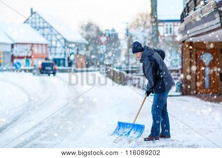 Man with snow shovel cleans sidewalks in winter