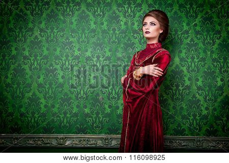 Woman In Vintage Clothes On Rococo Wall