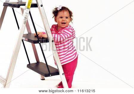 Baby standing by a ladder