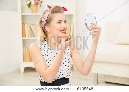 Young attractive girl putting lipstick on.